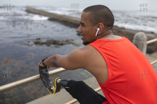 Disabled mixed race man with a prosthetic leg and running blade working out by the coast wearing wireless earphones, stretching with running blade up on a fence. Fitness disability healthy lifestyle.