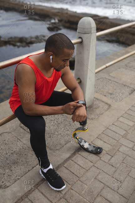 Disabled mixed race man with a prosthetic leg and running blade working out by the coast wearing wireless earphones, sitting on a fence and checking smartwatch. Fitness disability healthy lifestyle.