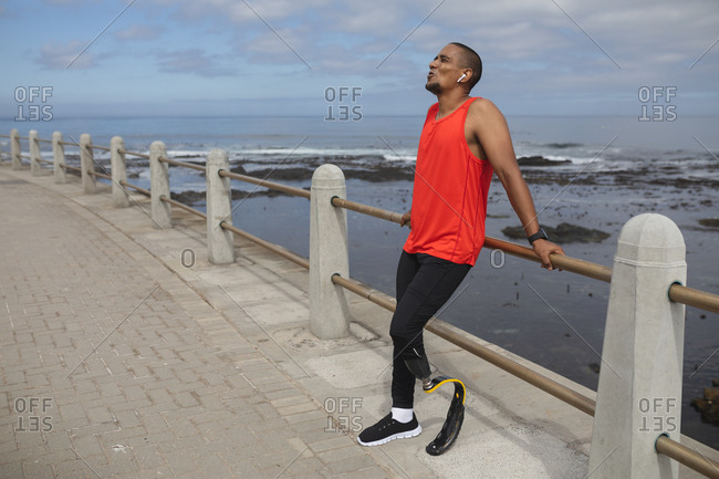 Disabled mixed race man with a prosthetic leg and running blade working out by the coast wearing wireless earphones, taking a break leaning on a fence. Fitness disability healthy lifestyle.