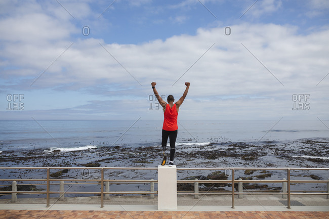 Rear view of disabled mixed race man with a prosthetic leg and running blade working out by the coast, standing on a fence looking out to sea with arms raised. Fitness disability healthy lifestyle.