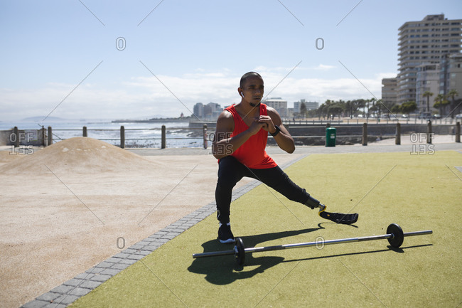 Disabled mixed race man with a prosthetic leg and running blade at an outdoor gym by the coast wearing wireless earphones, stretching legs, a barbell beside him. Fitness disability healthy lifestyle.