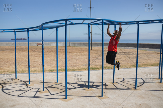Disabled mixed race man with a prosthetic leg and running blade exercising at an outdoor gym by the coast, working out on the monkey bars. Fitness disability healthy lifestyle.