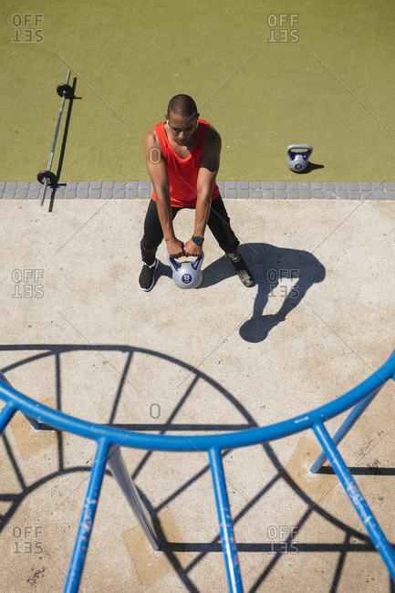 High angle view of disabled mixed race man with a prosthetic running blade working out at an outdoor gym wearing wireless earphones, swinging a kettlebell weight. Fitness disability healthy lifestyle.