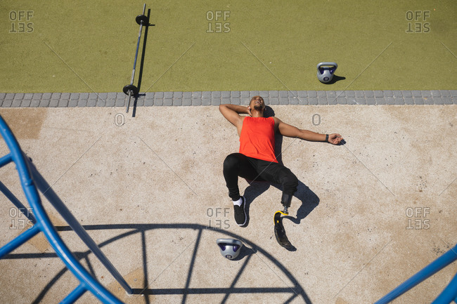 High angle view of disabled mixed race man with a prosthetic running blade working out at outdoor gym wearing wireless earphones, taking a rest lying on his back. Fitness disability healthy lifestyle.