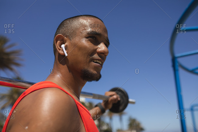 Confident mixed race man with a working out at an outdoor gym in the sun, wearing wireless earphones, holding weights on a barbell. Fitness disability healthy lifestyle.