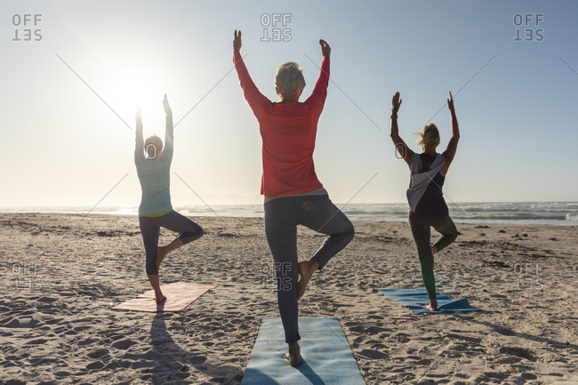 Group of Caucasian female friends enjoying exercising on a beach on a sunny day, practicing yoga, standing in tree position and facing the sea.
