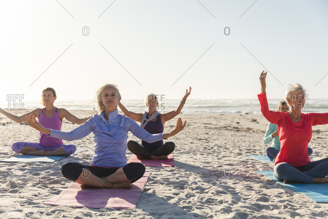 Group of Caucasian female friends enjoying exercising on a beach on a sunny day, practicing yoga, meditating in lotus position with sea in the background.