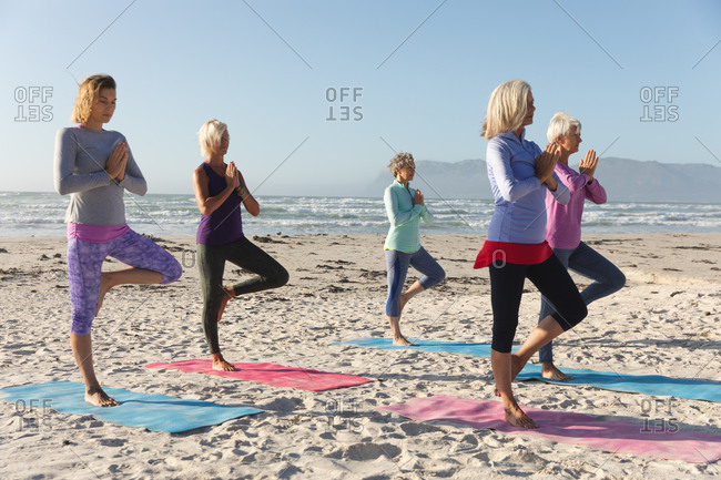 Group of Caucasian female friends enjoying exercising on a beach on a sunny day, practicing yoga, standing in tree position with sea in the background.