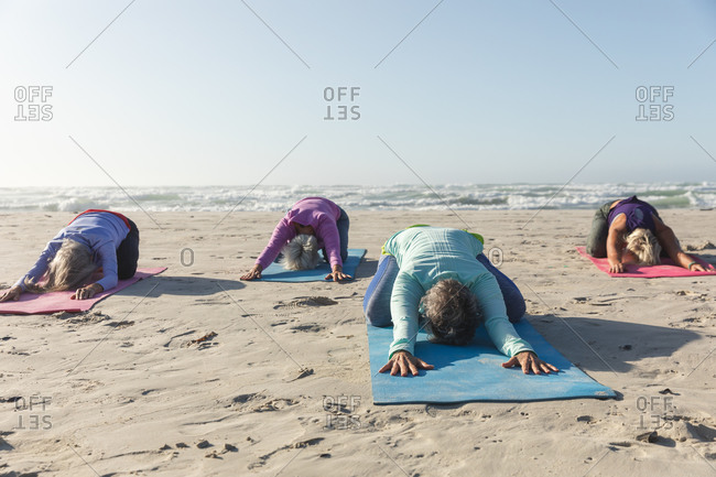 Group of Caucasian female friends enjoying exercising on a beach on a sunny day, practicing yoga and sitting in yoga position.