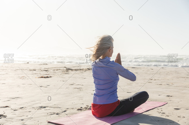 Caucasian woman with blond hair enjoying exercising on a beach on a sunny day, practicing yoga and sitting in yoga position.