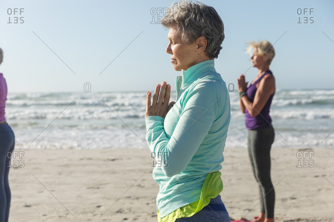 Group of Caucasian female friends enjoying exercising on a beach on a sunny day, practicing yoga and standing in yoga position.