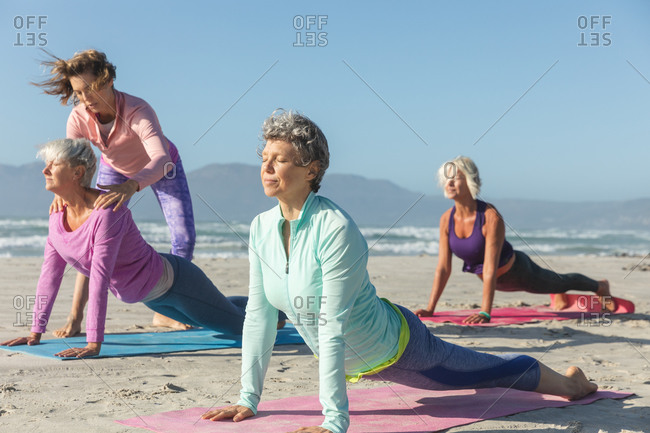Group of Caucasian female friends enjoying exercising on a beach on a sunny day, practicing yoga and stretching in yoga position.