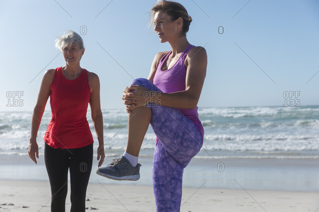 Two Caucasian female friends enjoying exercising on a beach on a sunny day, practicing yoga and stretching with sea in the background.
