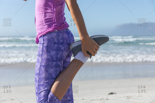 Mid section of a Caucasian woman enjoying exercising on a beach on a sunny day, practicing yoga and stretching with sea in the background.