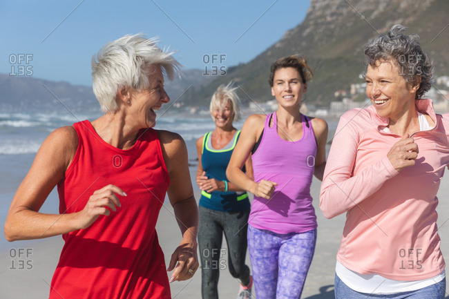 Group of Caucasian female friends enjoying exercising on a beach on a sunny day, running on the seashore and smiling.