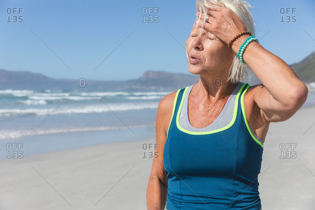 Senior Caucasian woman enjoying exercising on a beach on a sunny day, resting after running on the seashore and touching her forehead.