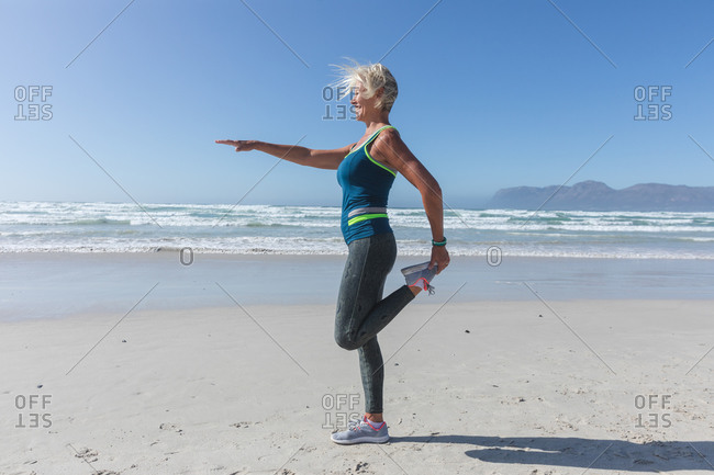 Senior Caucasian woman enjoying exercising on a beach on a sunny day, practicing yoga, standing in yoga position with sea in the background.