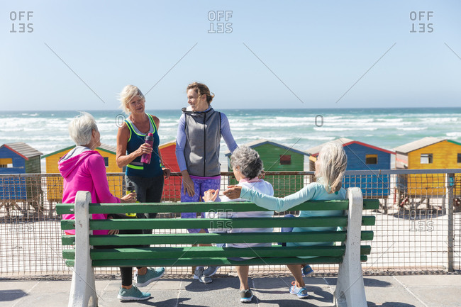 Group of a Caucasian female friends enjoying exercising on a beach on a sunny day, smiling, sitting on a bench on a promenade with little colorful houses in the background.