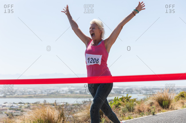 Senior Caucasian woman enjoying exercising on a sunny day, celebrating after running race and wearing numbers, running towards a finish line.