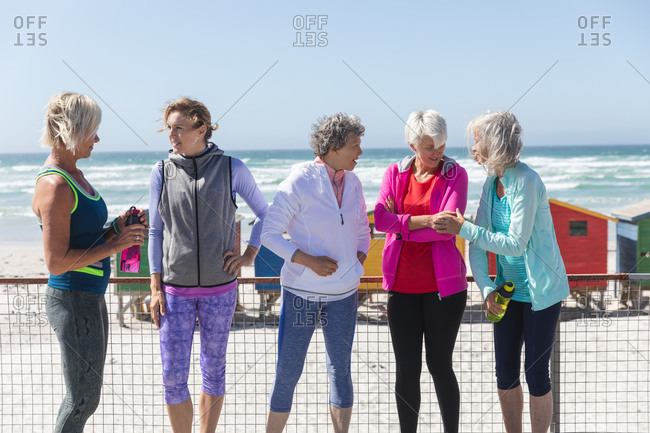 Group of a Caucasian female friends enjoying exercising on a beach on a sunny day, smiling, standing on a promenade with little colorful houses in the background.