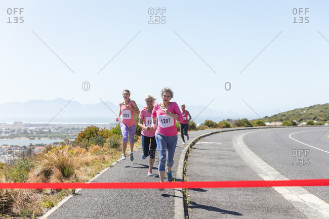 Group of Caucasian female friends enjoying exercising on a sunny day, having running race and wearing numbers, running towards a finish line.