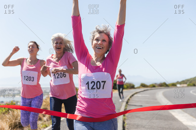 Group of Caucasian female friends enjoying exercising on a sunny day, having running race and wearing numbers, running towards a finish line and celebrating.