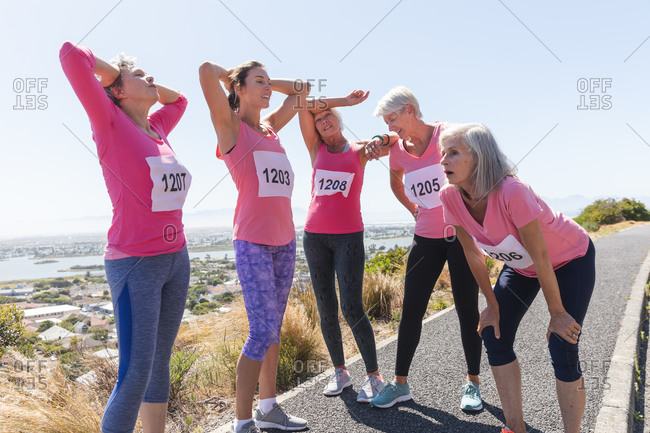 Group of Caucasian female friends enjoying exercising on a sunny day, taking a break after running race, wearing numbers and pink sportswear.