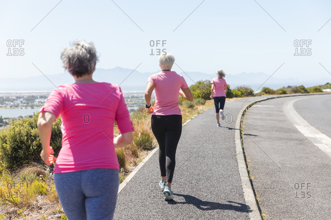 Group of Caucasian female friends enjoying exercising on a sunny day with blue sky, having running race and wearing pink sportswear.