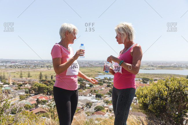 Two senior Caucasian female friends enjoying exercising on a sunny day, taking a break after running race, wearing numbers and pink sportswear, drinking water from a bottles.