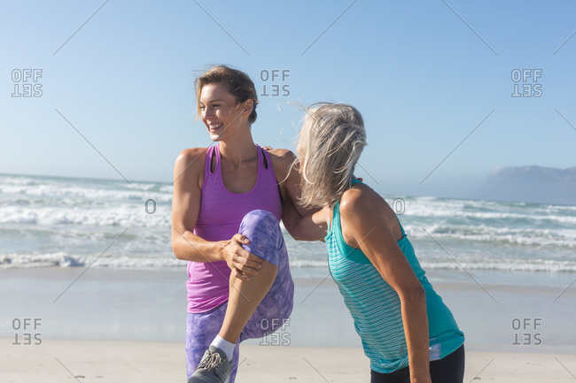 Group of Caucasian female friends enjoying exercising on a beach on a sunny day, practicing yoga and stretching with sea in the background.