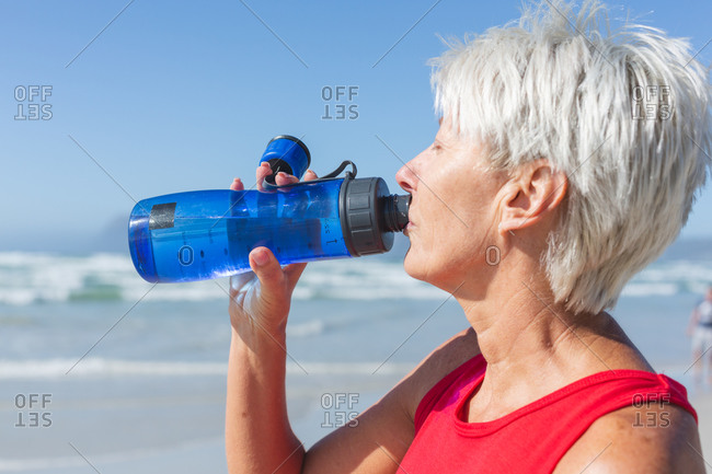 Senior Caucasian woman enjoying exercising on a beach on a sunny day, resting after running on the seashore and drinking water from a bottle.