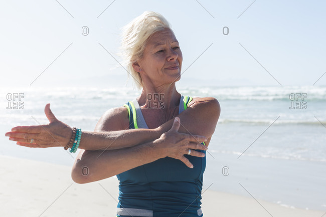 Senior Caucasian woman with blond hair enjoying exercising on a beach on a sunny day, practicing yoga and stretching with sea in the background.