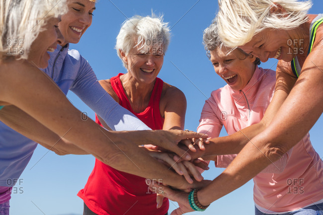 Group of happy Caucasian female friends enjoying exercising on a beach on a sunny day, smiling, standing and teaming up.