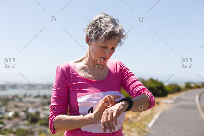 Senior Caucasian woman enjoying exercising on a sunny day, taking a break after running race, wearing numbers checking her smartwatch.