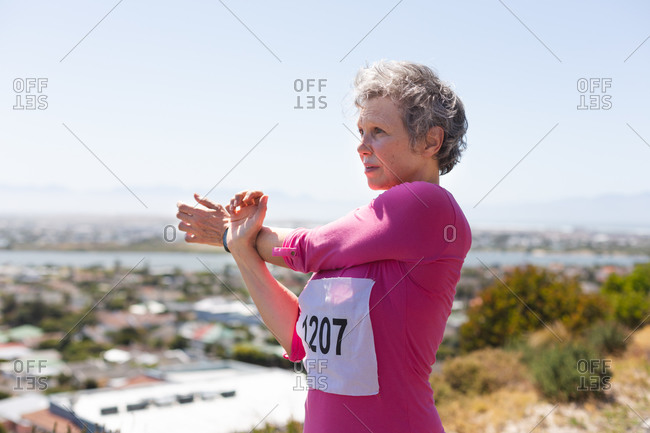 Senior Caucasian woman enjoying exercising on a sunny day, stretching before running race, wearing numbers and pink sportswear, with blue sky in the background.