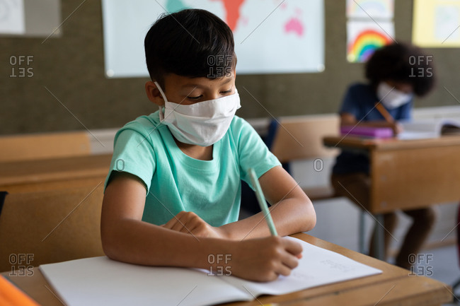 Two multi ethnic children sitting at desks wearing face masks in classroom. Primary education social distancing health safety during Covid19 Coronavirus pandemic.