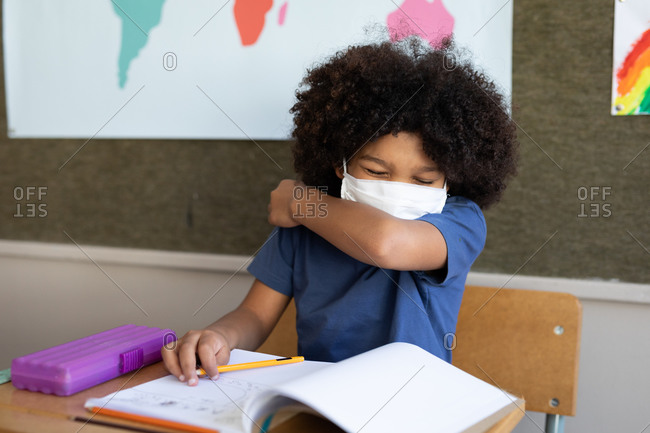 Mixed race boy sitting at desk wearing face mask in classroom, covering his face while sneezing. Primary education social distancing health safety during Covid19 Coronavirus pandemic.