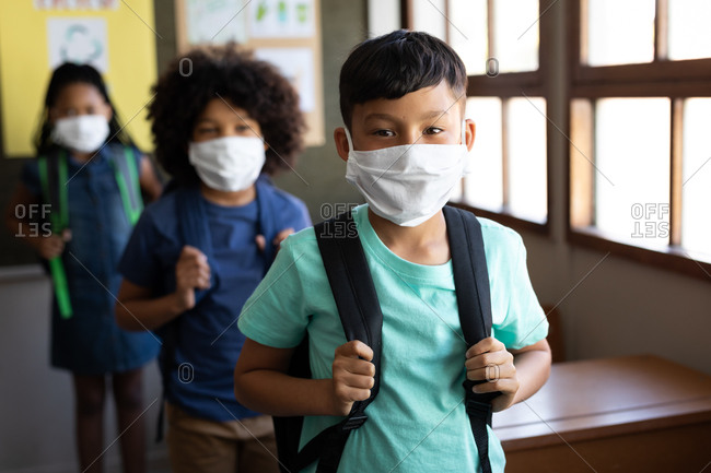 Multi ethnic group of elementary school children looking at camera, wearing face masks in school hall. Primary education social distancing health safety during Covid19 Coronavirus pandemic.