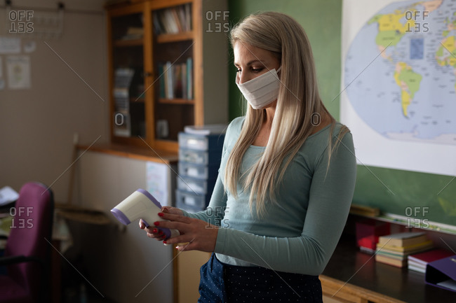 Caucasian female teacher wearing face mask getting ready to measuring temperature in an elementary school. Primary education social distancing health safety during Covid19 Coronavirus pandemic.