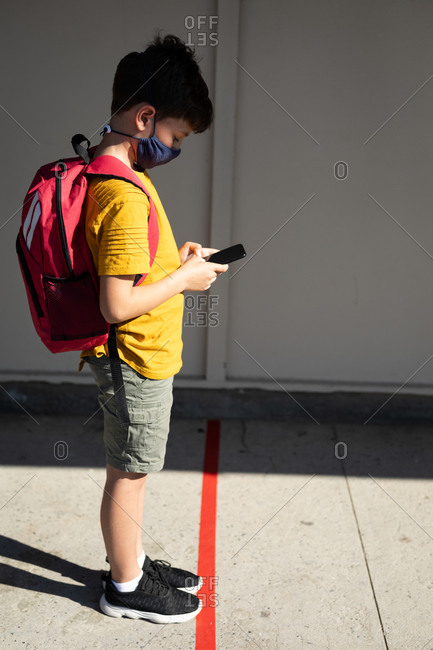 Caucasian boy wearing face mask, using his smartphone, maintaining social distancing at school. Primary education social distancing health safety during Covid19 Coronavirus pandemic.