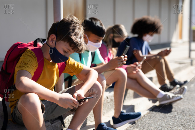 Multi ethnic group of elementary school kids wearing face masks using smartphones while sitting together. Primary education social distancing health safety during Covid19 Coronavirus pandemic.