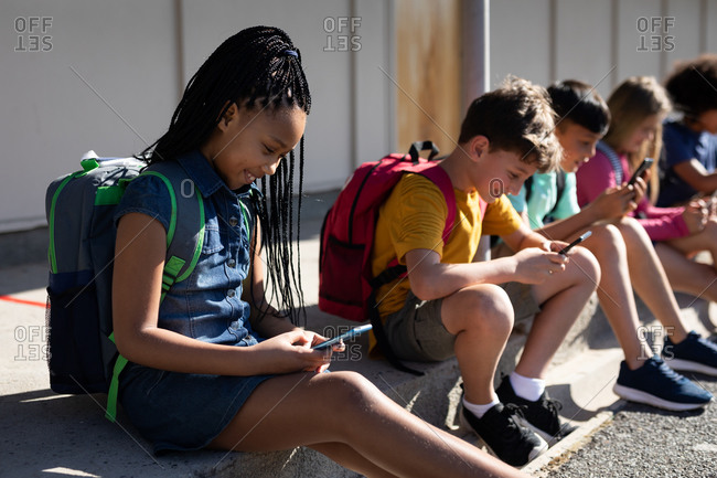 Multi ethnic group of elementary school kids using smartphones while sitting together. Primary education social distancing health safety during Covid19 Coronavirus pandemic.