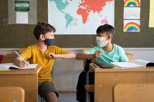 Two multi ethnic boys wearing face masks greeting each other by touching elbows in the classroom. Primary education social distancing health safety during Covid19 Coronavirus pandemic.