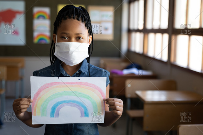 Portrait of a mixed race girl wearing face mask holding a rainbow drawing in the classroom. Primary education social distancing health safety during Covid19 Coronavirus pandemic.