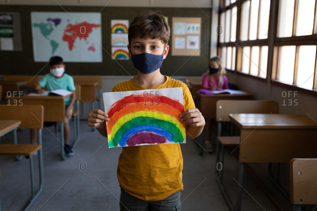 Portrait of a Caucasian boy wearing face mask holding a rainbow drawing in the classroom. Primary education social distancing health safety during Covid19 Coronavirus pandemic.