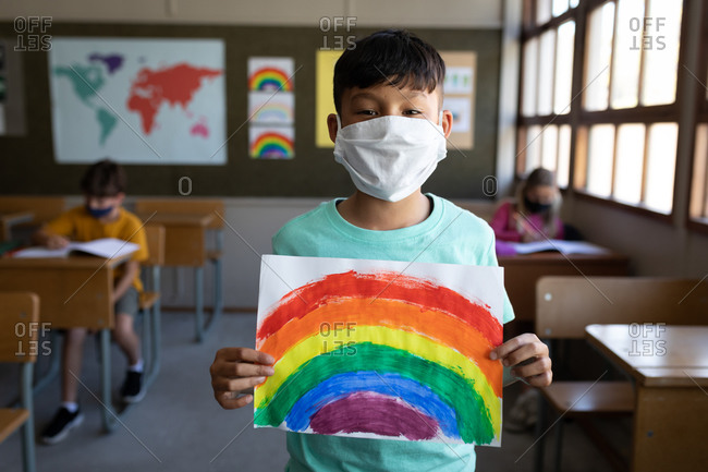 Portrait of a mixed race boy wearing face mask holding a rainbow drawing in the classroom. Primary education social distancing health safety during Covid19 Coronavirus pandemic.