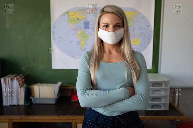 Portrait of a Caucasian female teacher wearing face mask standing with her arms crossed in class in the classroom. Primary education social distancing health safety during Covid19 Coronavirus pandemic