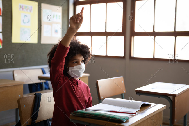 Mixed race boy wearing face mask, sitting on his desk during the lesson. Primary education social distancing health safety during Covid19 Coronavirus pandemic.