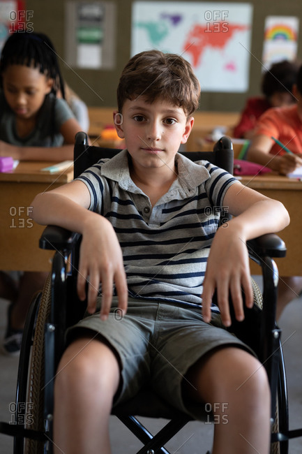 Portrait of disable Caucasian boy sitting in his wheelchair in the classroom during the lesson.  Primary education social distancing health safety during Covid19 Coronavirus pandemic.