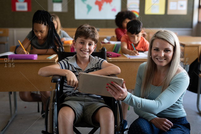 Portrait of disable Caucasian boy sitting in his wheelchair and his female teacher using tablet in the classroom. Primary education social distancing health safety during Covid19 Coronavirus pandemic.